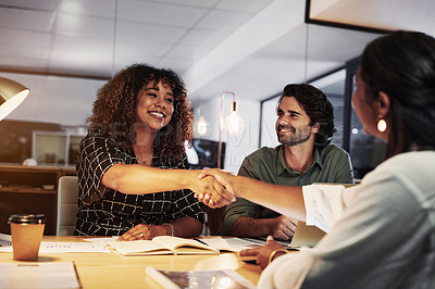 Buy stock photo Shot of colleagues shaking hands during a late night meeting in a modern office