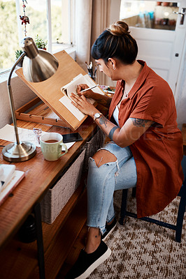Buy stock photo Full length shot of a young woman sketching at home