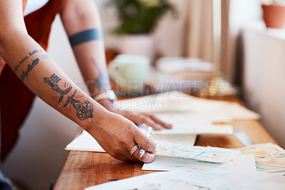 Buy stock photo Cropped shot of an unrecognizable woman looking at her sketches on a table at home