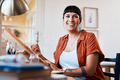 Buy stock photo Portrait shot of an unrecognizable woman working on a painting at home