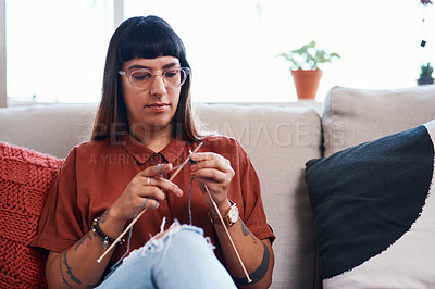 Buy stock photo Cropped shot of a young woman knitting while relaxing at home