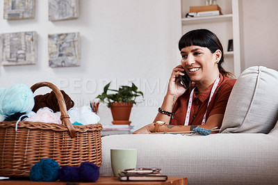 Buy stock photo Shot of a clothing designer talking on her phone while relaxing at home