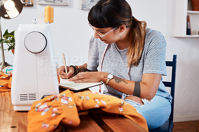 Buy stock photo Cropped shot of a young woman making notes while designing a garment at home