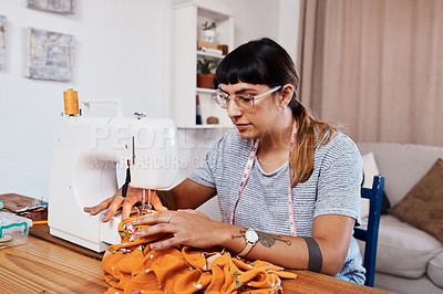 Buy stock photo Cropped shot of a young woman stitching fabric using a sewing machine at home
