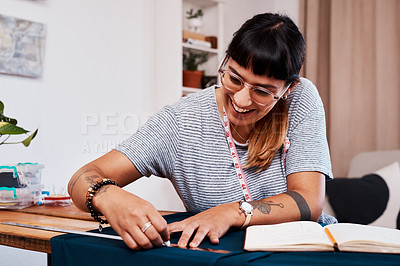 Buy stock photo Cropped shot of a young woman making a garment at home