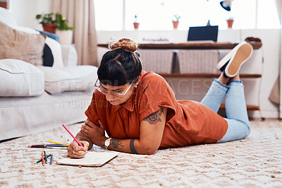 Buy stock photo Shot of a young woman using coloring pens while drawing at home