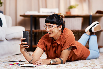 Buy stock photo Shot of a young woman taking a selfie while drawing at home