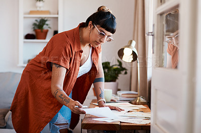 Buy stock photo Shot of a an artist looking at her sketches on a desk at home