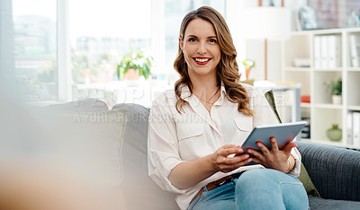 Buy stock photo Portrait of an attractive young businesswoman using a digital tablet while sitting on a sofa inside her office