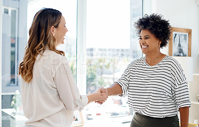 Buy stock photo Cropped shot of two attractive young businesswomen shaking hands together inside an office