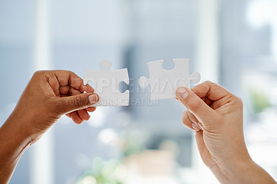 Buy stock photo Cropped shot of two unrecognizable businesswomen holding puzzle pieces inside an office