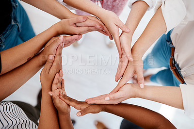 Buy stock photo Low angel shot of a group of unrecognizable businesspeople joining hands in circular formation inside an office