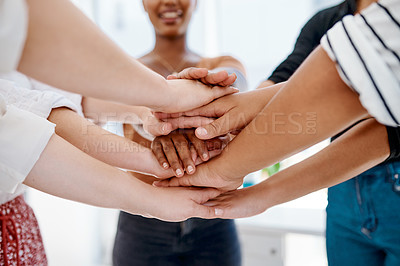 Buy stock photo Cropped shot of a group of unrecognizable businesspeople joining hands together in a huddle inside an office