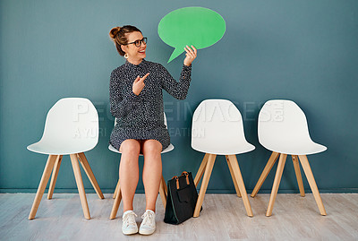 Buy stock photo Studio shot of an attractive young businesswoman pointing to a speech bubble while siting in line against a grey background