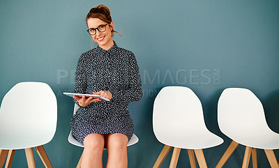 Buy stock photo Studio portrait of an attractive young businesswoman using a digital tablet while sitting in line against a grey background