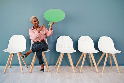 Buy stock photo Studio portrait of an attractive young businesswoman pointing to a speech bubble while siting in line against a grey background