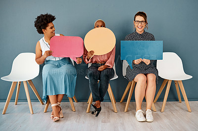 Buy stock photo Studio shot of a group of attractive young businesswomen holding speech bubbles while sitting in a row against a grey background