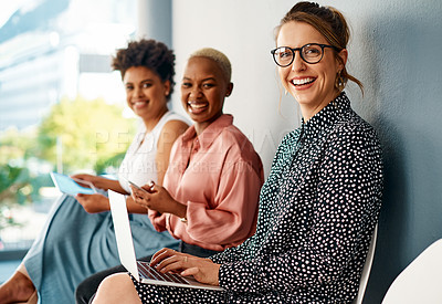 Buy stock photo Cropped portrait of a group of attractive young businesswomen using wireless technology while sitting in line in a modern office