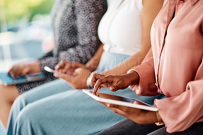 Buy stock photo Cropped shot of a group of unrecognizable businesswomen using wireless technology while sitting in line in a modern office