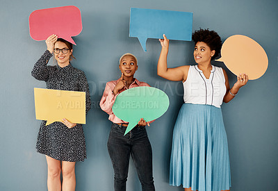 Buy stock photo Studio shot of a group of attractive young businesswomen holding speech bubbles while standing against a grey background