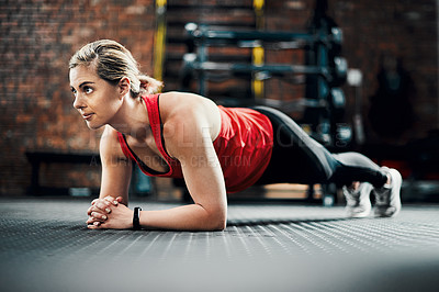 Buy stock photo Full length shot of an attractive young female athlete planking in the gym