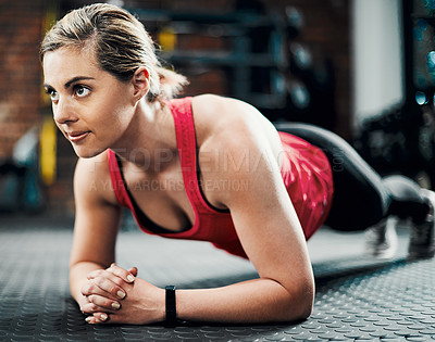 Buy stock photo Cropped shot of an attractive young female athlete planking in the gym