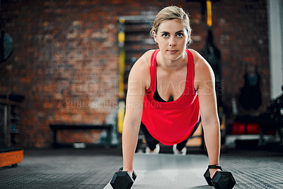 Buy stock photo Full length shot of an attractive young female athlete working out with dumbbells in the gym