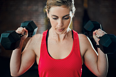 Buy stock photo Cropped shot of an attractive young female athlete working out with dumbbells in the gym