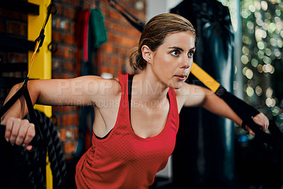 Buy stock photo Cropped shot of an attractive young female athlete doing cable flies in the gym