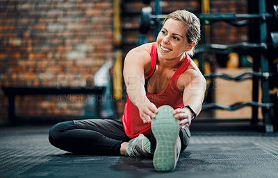 Buy stock photo Full length shot of an attractive young female athlete stretching before starting her workout in the gym