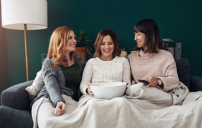 Buy stock photo Portrait of three middle aged women having a girls night at home while eating popcorn and watching movies