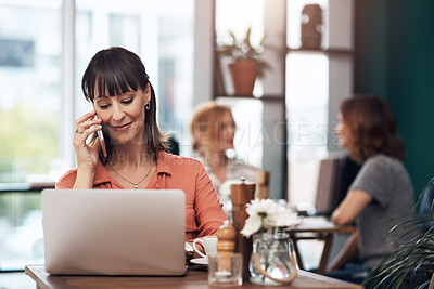 Buy stock photo Cropped shot of an attractive middle aged woman talking on her cellphone while working on a laptop inside of a coffee shop during the day