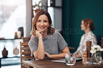Buy stock photo Portrait of an attractive middle aged woman seated inside of a coffee shop by herself during the day
