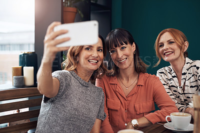 Buy stock photo Cropped shot of a group of attractive middle aged women taking a self portrait together while being seated inside of a coffee shop during the day