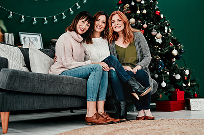Buy stock photo Portrait of three attractive middle aged women seated together on a sofa with a Christmas tree in the background at home