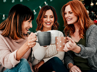 Buy stock photo Cropped shot of three attractive middle aged women seated on a sofa together while drinking coffee at home during Christmas time