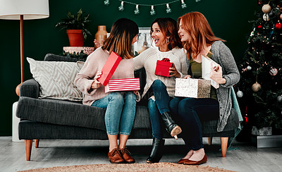 Buy stock photo Shot of three attractive middle aged women opening presents together while being seated on a sofa during Christmas time
