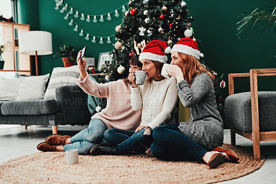 Buy stock photo Shot of three attractive middle aged women taking self portraits together with a cellphone at home during Christmas time