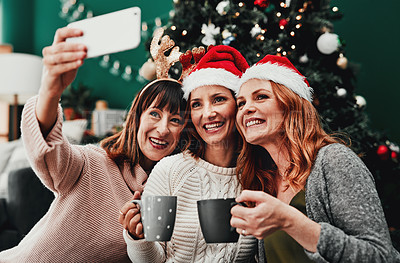 Buy stock photo Cropped shot of three attractive middle aged women taking self portraits together with a cellphone at home during Christmas time