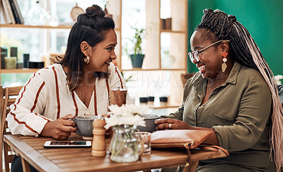 Buy stock photo Shot of two young women chatting at a cafe