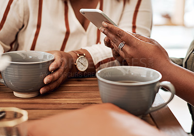Buy stock photo Cropped shot of two women using a smartphone together at a cafe