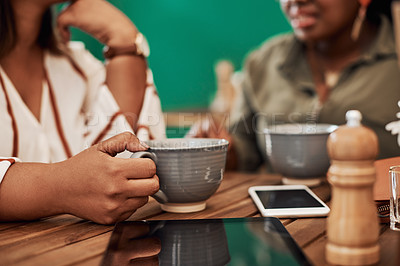 Buy stock photo Cropped shot of two women chatting and having coffee at a cafe