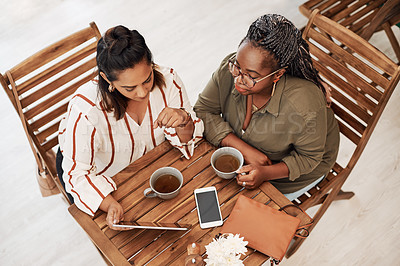 Buy stock photo High angle shot of two young women using a digital tablet together at a cafe