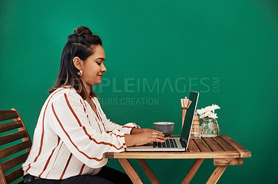 Buy stock photo Shot of a young woman using a laptop at a cafe