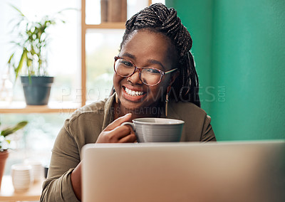 Buy stock photo Shot of a young woman having coffee and using a laptop at a cafe