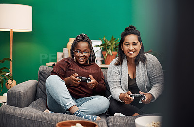 Buy stock photo Shot of two young women playing video games on the sofa at home