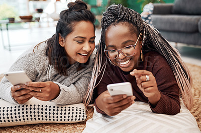Buy stock photo Shot of two young women using their smartphones on the floor at home