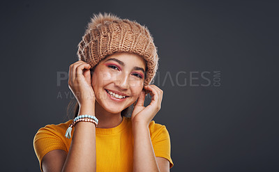 Buy stock photo Cropped portrait of an attractive teenage girl wearing a beanie and standing against a dark background in the studio alone