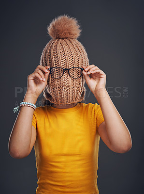 Buy stock photo Cropped shot of an unrecognizable teenage girl wearing a beanie and feeling playful against a dark studio background