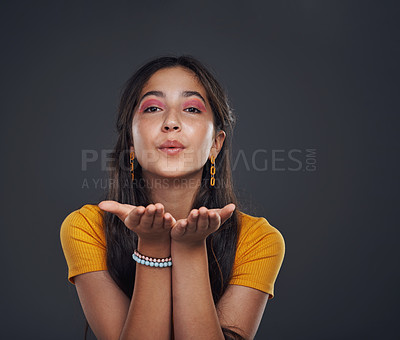 Buy stock photo Cropped portrait of an attractive teenage girl standing alone and blowing kisses against a dark studio background